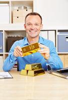 Mann hält Goldbarren in seiner Hand
