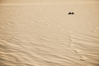Old used black boots lie half buried in desert sand dune under clear sunny sky