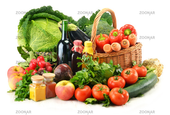 Raw vegetables and wicker basket isolated on white