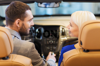 happy couple sitting in car at auto show or salon