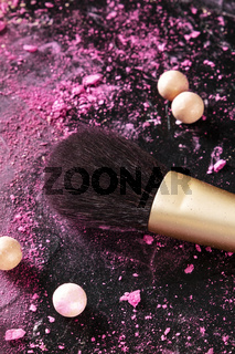 A makeup brush with crushed cosmetics and pearls on a dark background, with a place for text