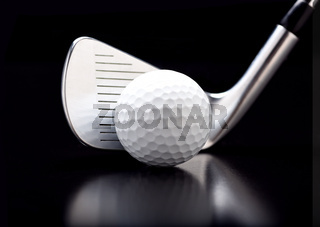 Closeup of a nine iron with a golf ball on black with reflection.