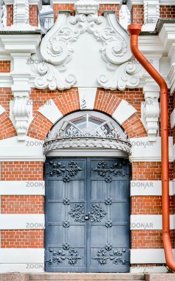 Brick wall of historical building, stucco molding, wrought iron door