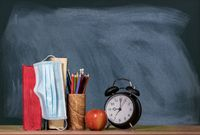 Back to virtual school background concept with stack of books, apple and alarm clock with face mask