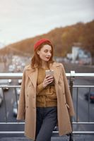 Tender young woman warming up with cup of coffee on the street female fashion standing on a pedestrian bridge. Portrait of stylish young woman wearing autumn coat and red beret outdoors. Toned image