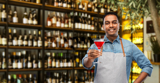 indian barman with glass of cocktail at bar