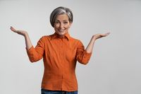 Cheerful woman with gray hair spreads her bent arms and smiles at camera while showing at copy spaces at both sides. Adult woman in orange shirt on an isolated background. High quality photo