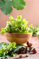 Green hazelnut in a wooden bowl.