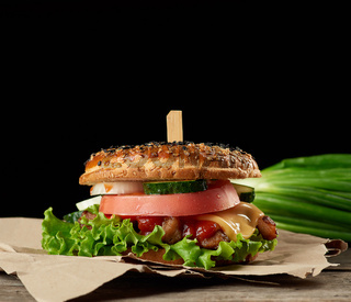 cheeseburger with minced meat, green lettuce and ketchup