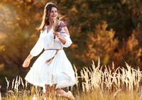 Young woman dancing in the grass and back light