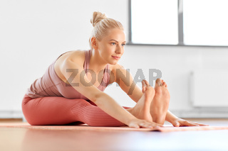 woman doing yoga and seated forward bend at home