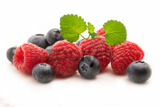Fresh blueberries and raspberries with lemon balm leaf isolated