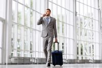 businessman with travel bag calling on smartphone