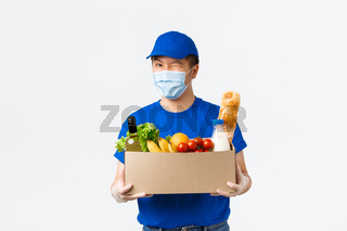 Online shopping, food delivery and covid-19 pandemic concept. Cheerful asian male courier provide fast shipping, holding box with groceries, bring order to client, wear medical mask and gloves