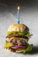 Cheeseburger mit brennender Kerze