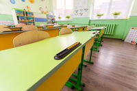 Wide angle desks and chairs in classroom.