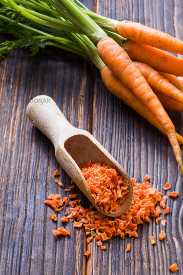 Wooden scoop with ground condiment made of carrots