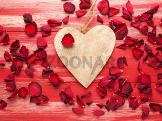 Rustic wooden heart with rose petals on wood