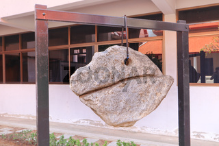Decorative lucky rock boulder hanging on a chain in Buddhist temple, Thailand.