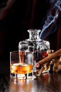 Whisky in glass with ice cubes and a smoking cigar