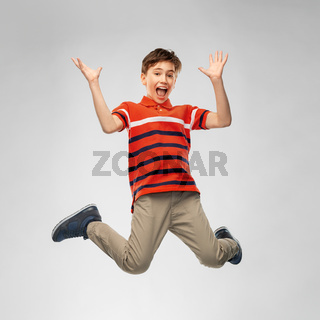 happy smiling young boy jumping in air