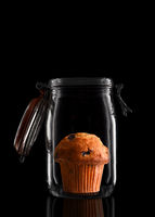 A Blueberry Muffin in a glass storage or canning jar isolated on black with reflection, with lid ope