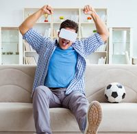 Man wearing virtual reality VR glasses watching soccer football