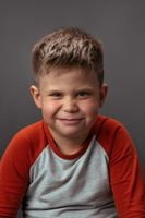 Preschool boy smiling with smirk at camera. Portrait of funny child on gray background. Emotions concept