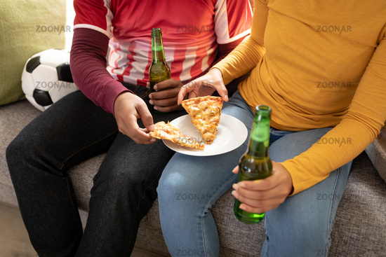 Mid section of having beer and pizza while sitting on couch at home