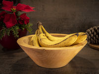 A turned rustic light wooden bowl with bananas stands on a dark surface with flowers in the backgrou