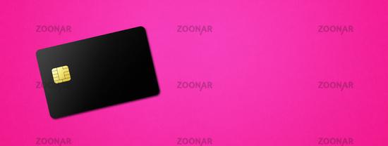 Black credit card on pink background