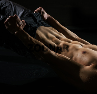 Athletic man taking shower studio portrait