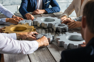 Business people joining gears