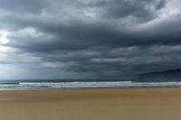 empty and large beautiful golden sand beach underneath a bad weather sky