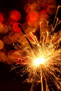 Burning sparkler against golden bokeh