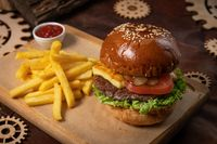 Beef burger are served with french fries on a decorative wooden board with tomato sauce with wooden decorative pieces of simple mechanism. Restaurant, Fast food concept. Street food concept
