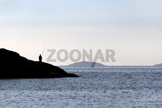 Silhouette of a Fisherman standing on rocks with fishing rod near sea