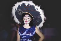 Woman dressed as catrina with flower skull make up and big hat for day of the dead, Merida, Mexico
