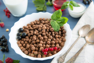 Sweet Cocoa Chocolate Sugar Cereal Puffs with Milk Healthy tasty breakfast chocolate balls with strawberries, raspberries, black currants and red currants.