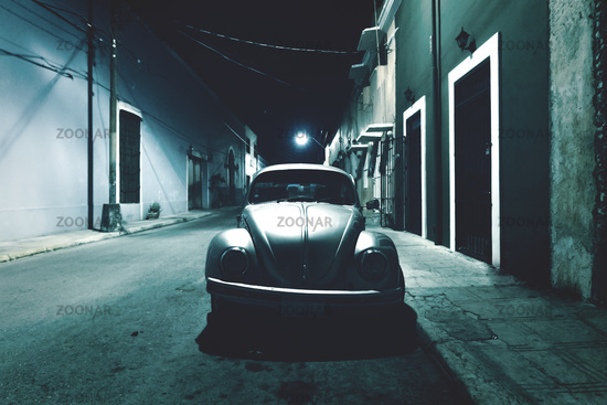 Silver old vintage Volkswagen beetle at night in the colonial streets of Merida, Yucatan, Mexico