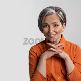 Mature woman in orange shirt smiles at camera. Female hands are folded into the castle. Isolated background of photo studio. High quality photo