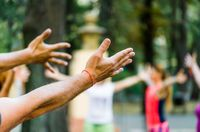 hands of people are raised up yoga in the park