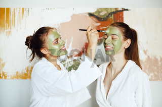 Female friends applying skin care masks on face