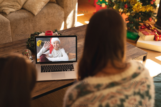 Rear view of woman and son having a videocall with woman in santa hat waving on laptop at home