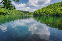 Beautiful turquoise water with puffy clouds reflected in a lake in Plitvice Lakes