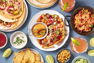 Mexican food, a flat lay. Nachos, tortillas, Paloma cocktails and other dishes, shot from the top