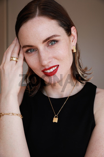 Smiling caucasian young woman wearing golden jewellery. Vertical close-up of beautiful woman.