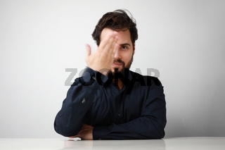 Handsome young man with beard in blue shirt looking with happy expression in camera and moving his hand.
