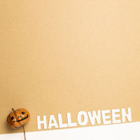Pumpkin and Halloween text on brown background. top view, copy space