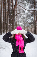 A girl in a pink scarf and hat stands in the middle of a pine forest and covers her face with white mittens. Beautiful pine forest on a frosty day.